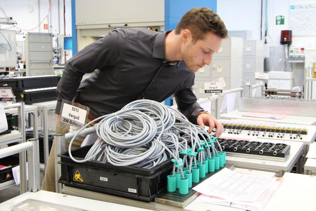 Patrick schaut sich in unserer Produktion die vergossenen Sensoren an.